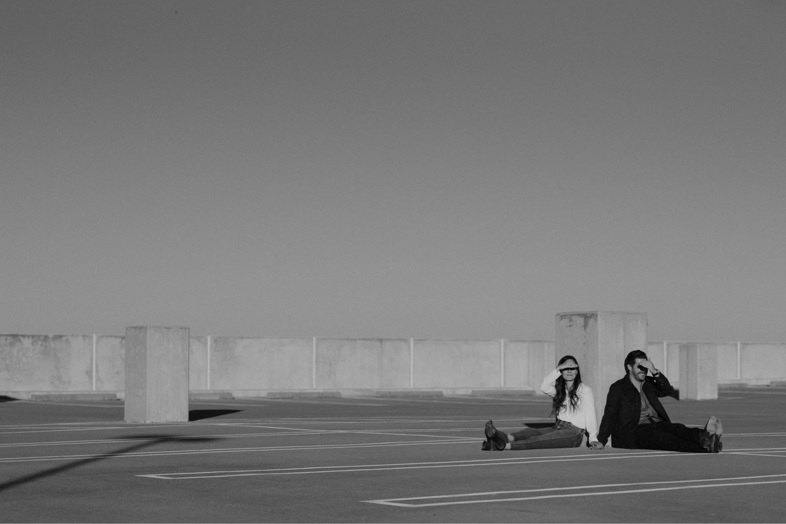 Alternative engagement session photography with couple sitting on parking structure in Mueller Park shading their eyes from the sun