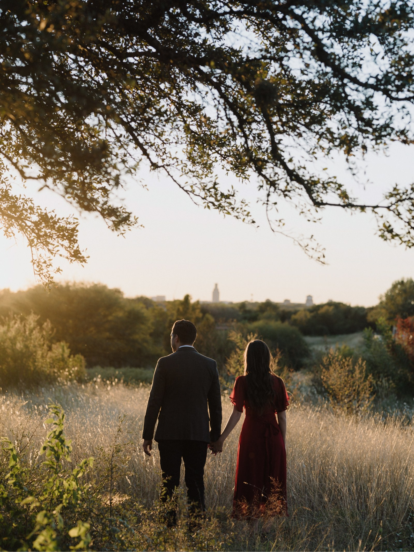 Sunset engagement photography session at Mueller Park in Austin with couple holding hands looking towards downtown