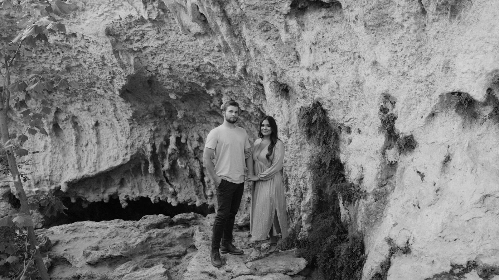 Romantic engagement shoot in a rock canyon by the Pedernales River in the Texas hill country