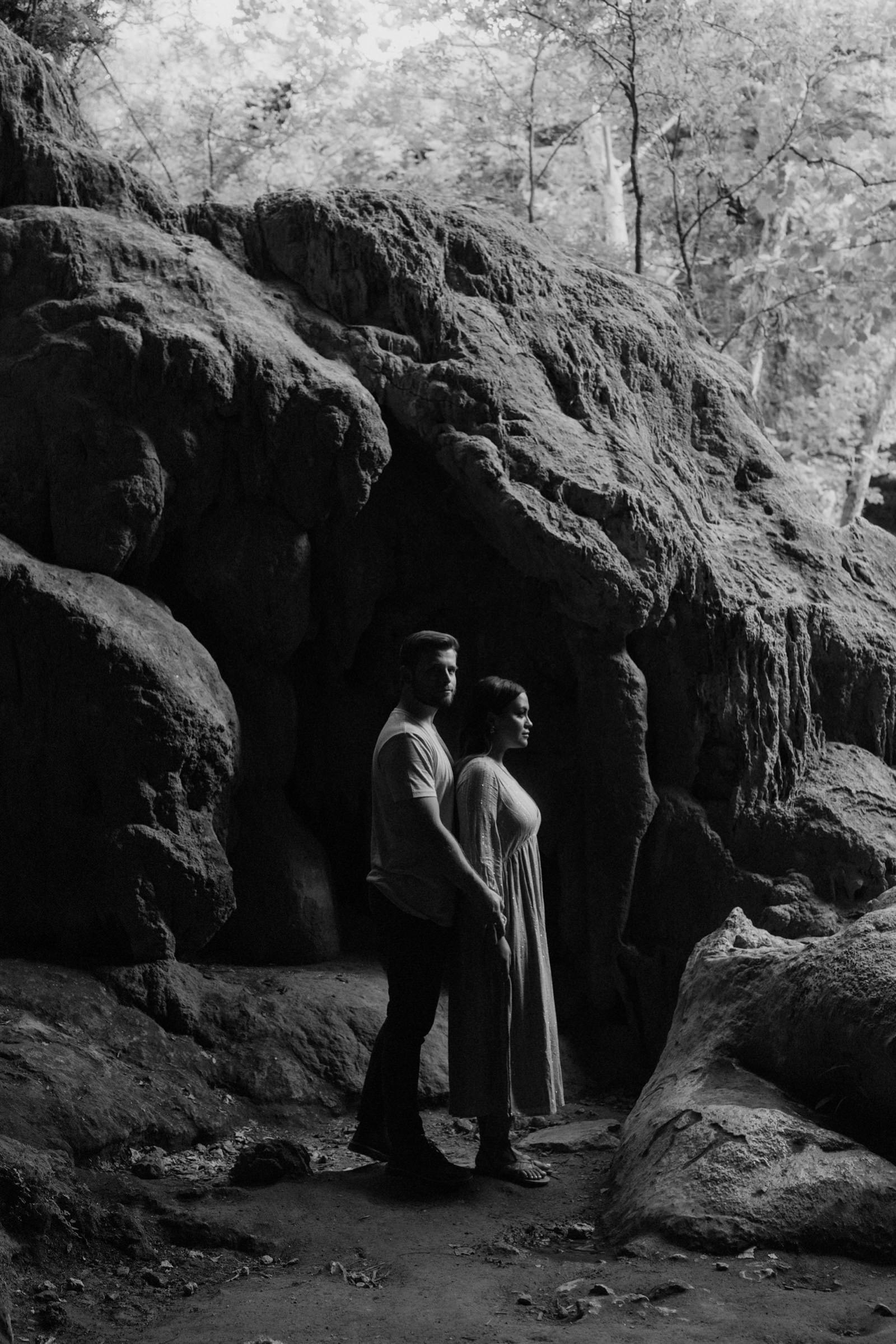 Black and white engagement photography in a remote Texas cave with the couple rim lit