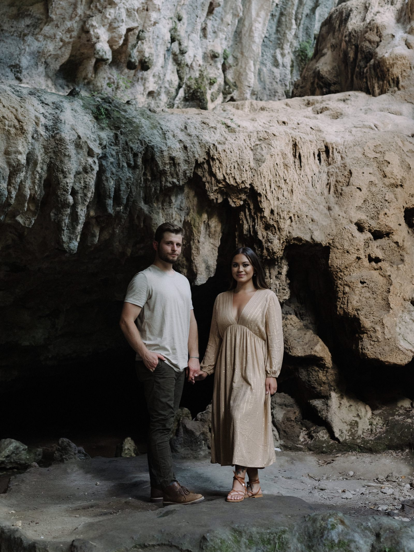 Timeless engagement session in a Hill Country canyon with him wearing casual clothes and her in a subtle beige draped dress