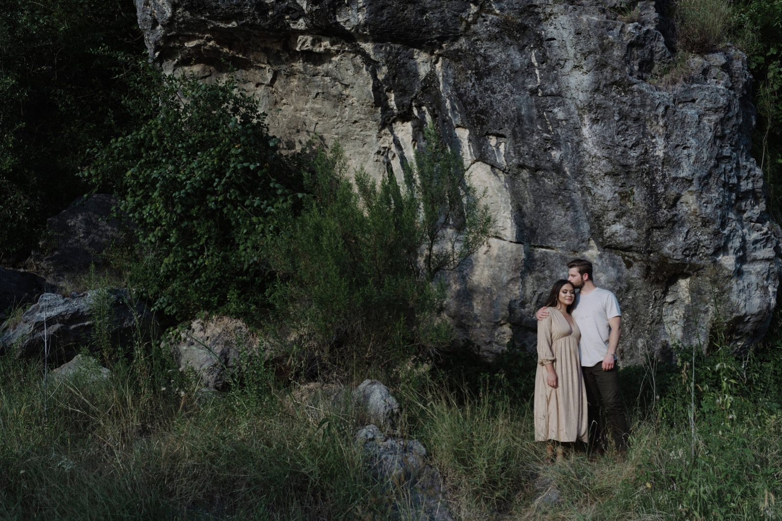 Engaged couple embracing outside a canyon in the Texas hill country during their photography session